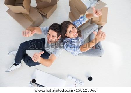 Overview of a couple giving thumbs up sitting in their new house - stock photo
