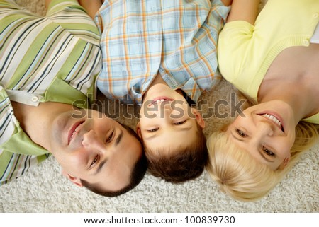 Overview of a happy family lying on the carpet - stock photo