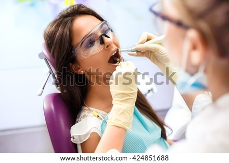 Overview of dental caries prevention.Woman at the dentist's chair during a dental procedure. Beautiful Woman smile close up. Healthy Smile. Beautiful Female Smile - stock photo
