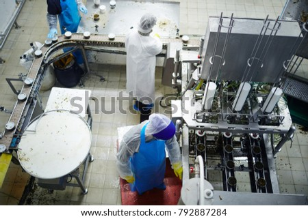 Overview of producing-line in seafood production plant with staff in uniform working there