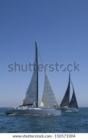 Overview of sailboats racing in the blue and calm ocean against sky - stock photo