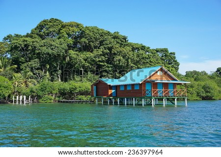 Overwater bungalow with lush tropical vegetation in background, Caribbean, Bocas del Toro, Panama - stock photo