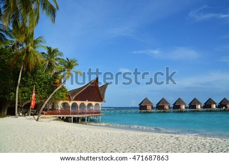 Overwater Bungalows and jetty in blue lagoon around tropical Island of maldives