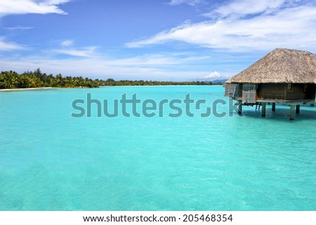 Overwater bungalows on the green tropical beach with steps into water, Bora Bora in French Polynesia. - stock photo