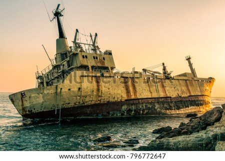 Overwater shipwreck at rocky shore with sun setting behind Mediterranean sea in the background. HDR shot.
