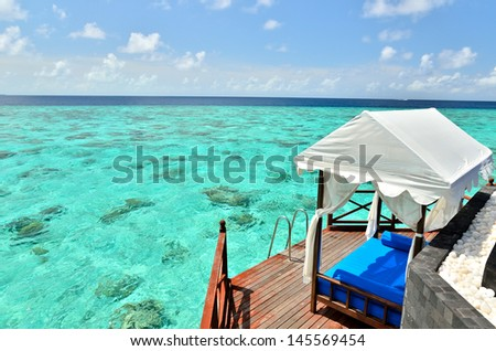 Overwater villa balcony overlooking tropical sea - stock photo