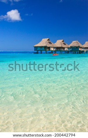 Overwater villas in blue tropical lagoon,  Bora Bora, French Polynesia, South Pacific - stock photo