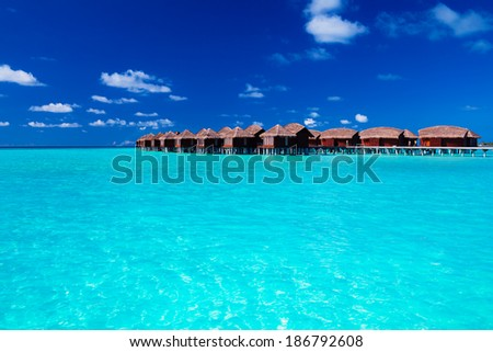 Overwater villas in blue tropical lagoon of shallow water - stock photo