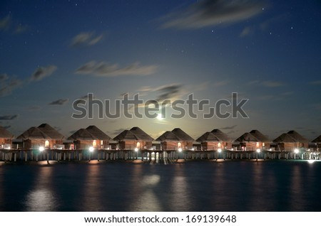 Overwater villas on the tropical lagoon in night   - stock photo