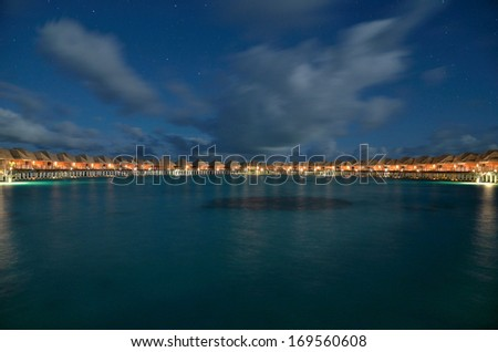 Overwater villas on the tropical lagoon in night -- Overwater villas panorama  - stock photo