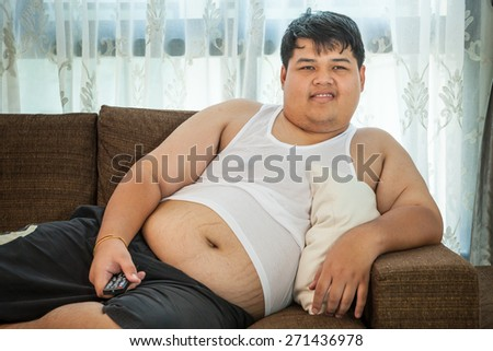 Overweight asian guy sitting on the couch with remote in hand trying to watch some TV - stock photo