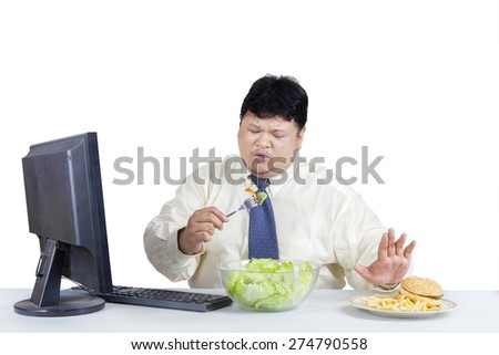 Overweight businessman avoid junk food and choose to eat salad - stock photo