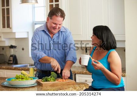 Overweight Couple On Diet Preparing Vegetables In Kitchen - stock photo