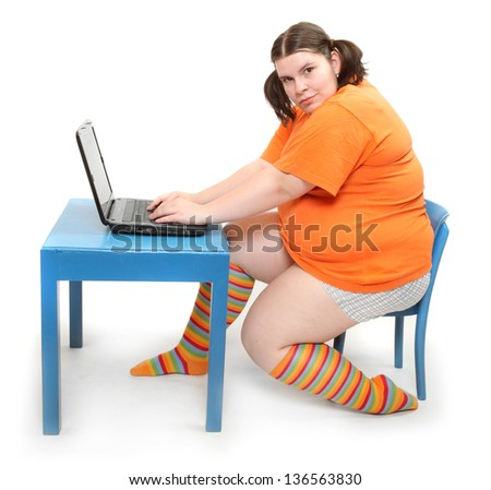 Overweight girl in a school desk with laptop. - stock photo
