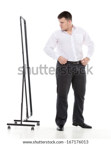 Overweight man admiring himself in a standing mirror as he checks the fit of his clothing and his appearance while dressing in the morning