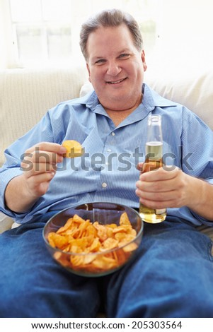 Overweight Man At Home Eating Chips And Drinking Beer - stock photo