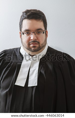 Overweight man in canadian lawyer toga against a white background - stock photo