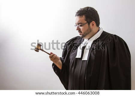 Overweight man in canadian lawyer toga, looking intensely at a gavel in his hand - stock photo