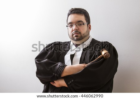Overweight man in canadian lawyer toga, with arms cross, holding a gavel in his hand - stock photo