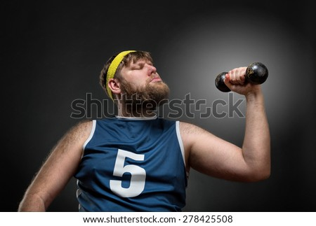 Overweight man lifts a dumbbell  - stock photo