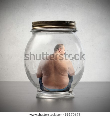 Overweight man sitting in a jar - stock photo