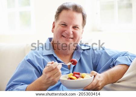 Overweight Man Sitting On Sofa Eating Bowl Of Fresh Fruit - stock photo