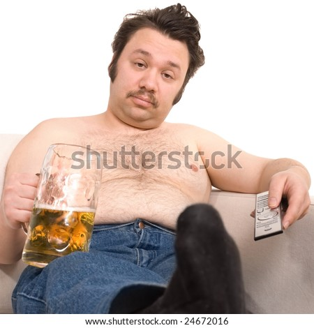 Overweight man sitting on the couch with a beer glass - stock photo