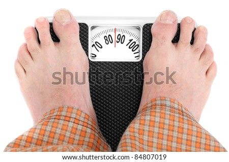 Overweight man standing on a retro style weighing machine isolated on a white background.