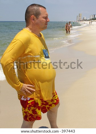 Overweight man striking a pose to impress girls on the beach - stock photo