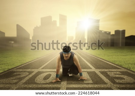 Overweight man try to loss weight by running on track in the morning with number 2015 - stock photo