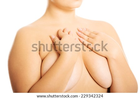 Overweight woman covering her breast. - stock photo