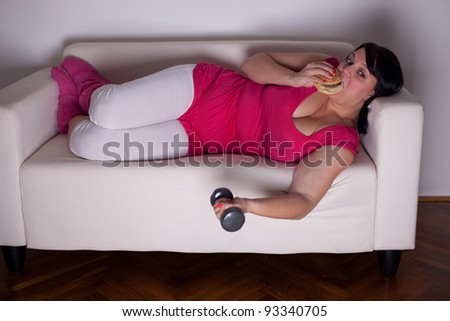 Overweight woman eating a burger, watching tv and lifting weights. Selective focus. - stock photo