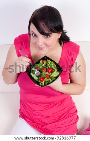 Overweight woman eating a salad. Selective focus. - stock photo