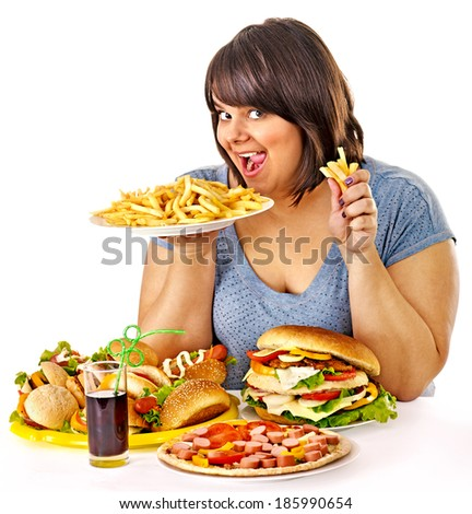 Overweight woman eating fast food. - stock photo