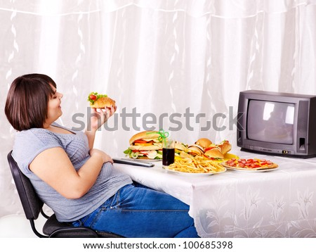 Overweight woman eating fast food and watching TV. - stock photo