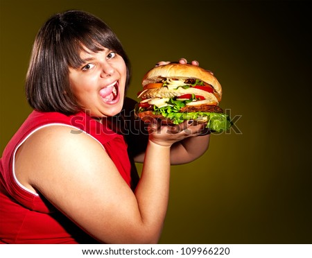 Overweight woman eating hamburger.