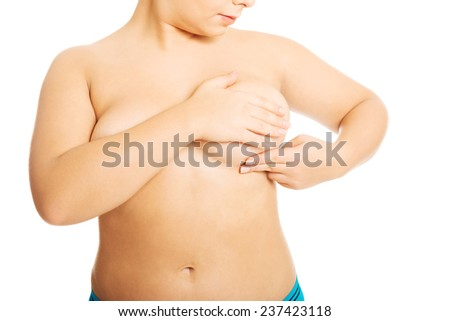 Overweight woman examining her breast.