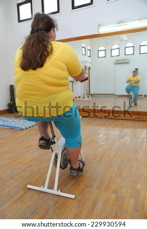 overweight woman exercising on bike simulator from behind - stock photo