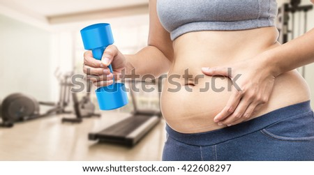 overweight woman hand holding fat belly and dumbbell