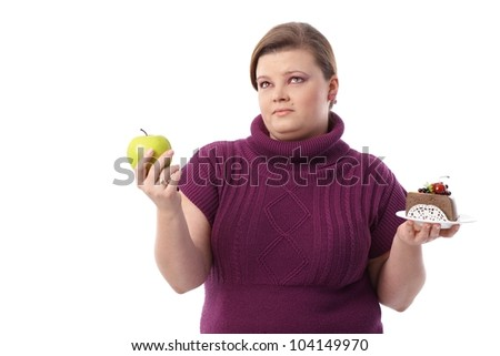 Overweight woman hesitating between green apple and chocolate cake. - stock photo
