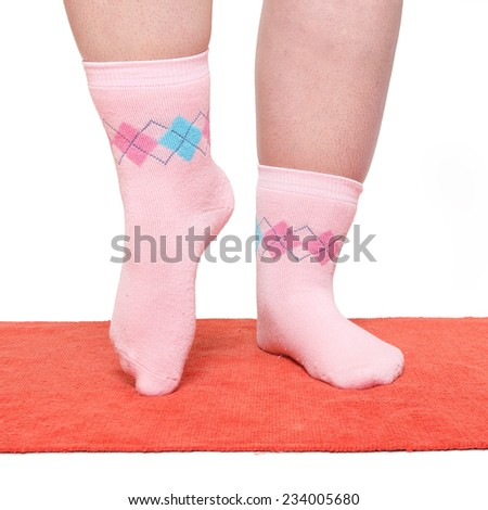 Overweight woman in funny socks excercising on red carpet. - stock photo