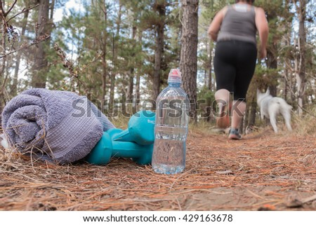 Overweight woman jogging on a forest trail to combat obesity with dog - stock photo