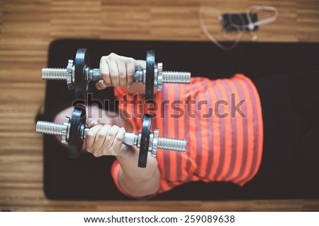 Overweight woman lifting weights - stock photo