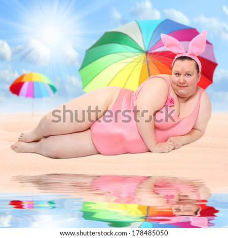 Overweight woman relaxing on a tropical beach. - stock photo