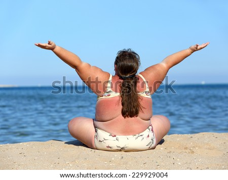 overweight woman sitting on beach with hands up  - stock photo