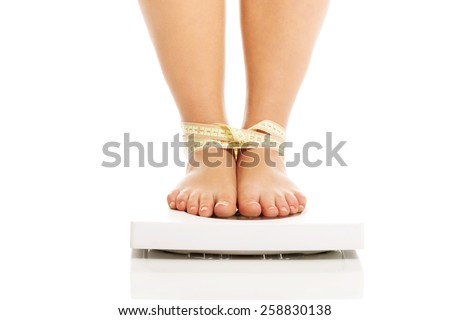 Overweight woman standing on a scale - stock photo