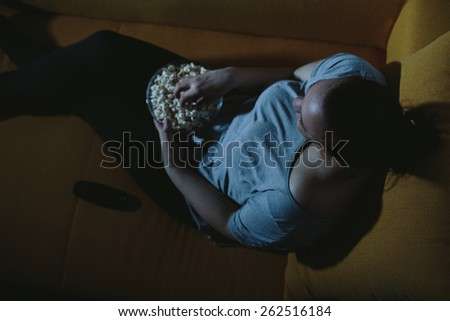 Overweight woman watching TV eating popcorn - stock photo
