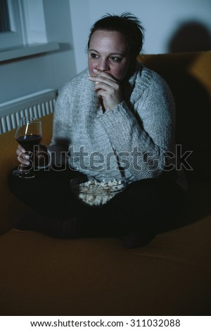 Overweight woman watching TV eating popcorn drinking wine - stock photo