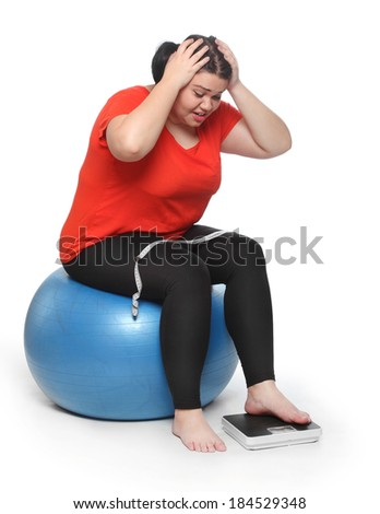 Overweight woman with a weighing machine and measure tape.  - stock photo