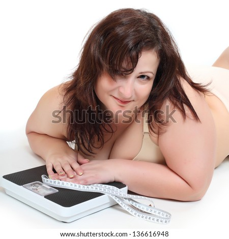 Overweight woman with measure tape and weghing machine. - stock photo